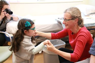 Dr. Penny Hogarth in clinic with a young visitor.