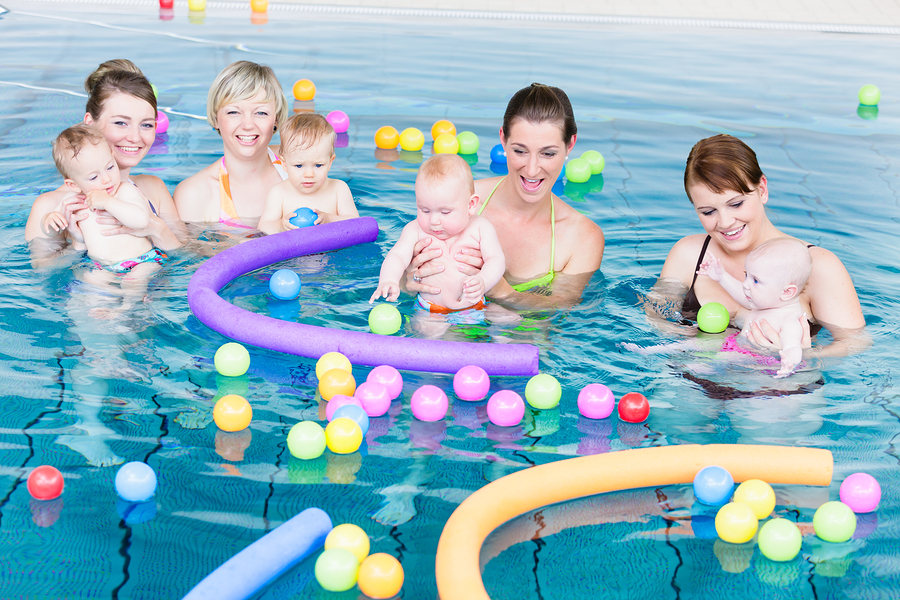 Moms and newborns playing in a pool