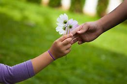 An adult is passing a bouquet of flowers to a child, standing in a lush green lawn