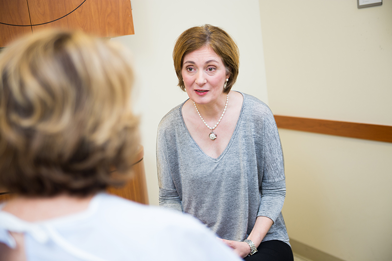 Dr. Tanja Pejovic speaking with a patient in an exam room.