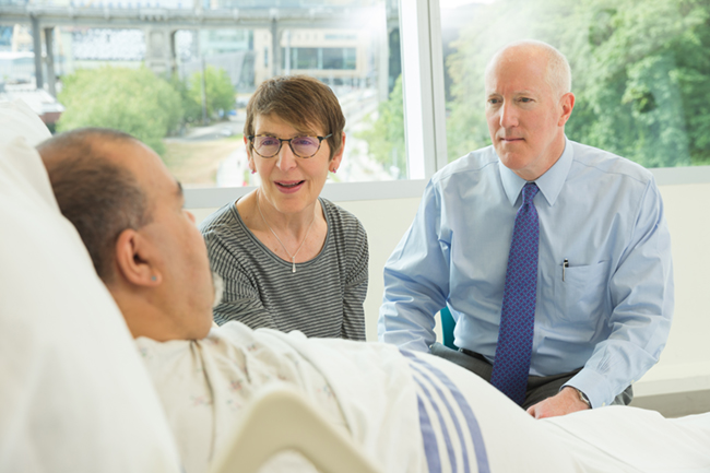 An OHSU Palliative Care Social Worker and OHSU Physician discuss care options with a patient