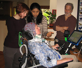 two women and a man standing around a person in a wheelchair with an electrode cap on