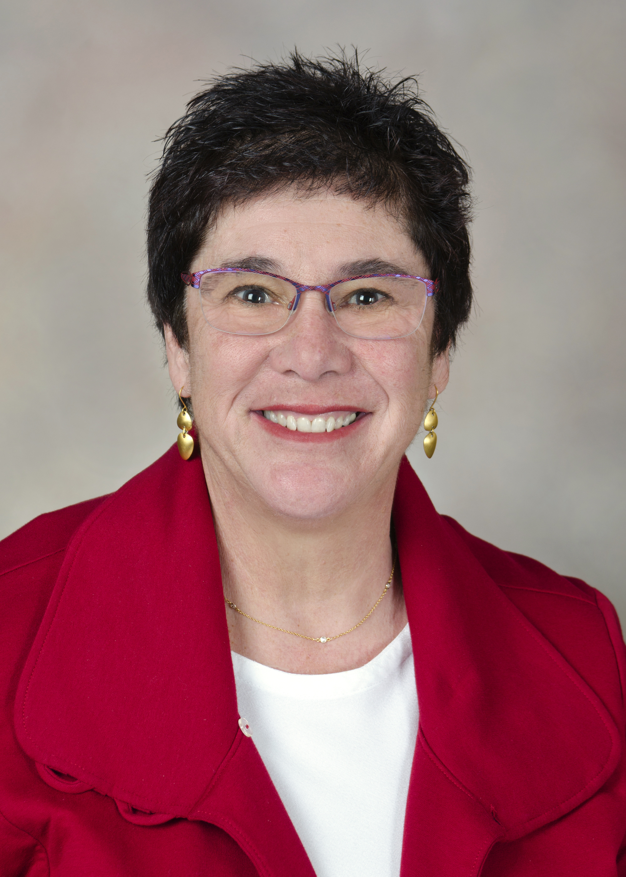 This is an image of Dr. Melanie Fried-Oken, a smiling woman in her 60's with short dark hair and a red jacket.
