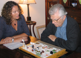 Woman with curly hair and man with gray hair using communication board