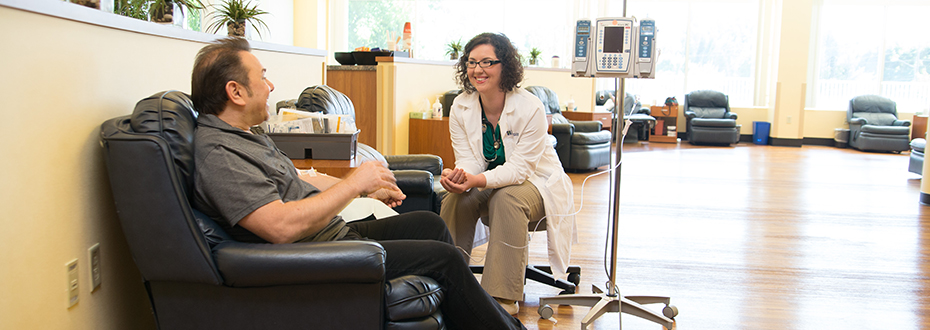 A doctor chats with a patient while he receives an infusion