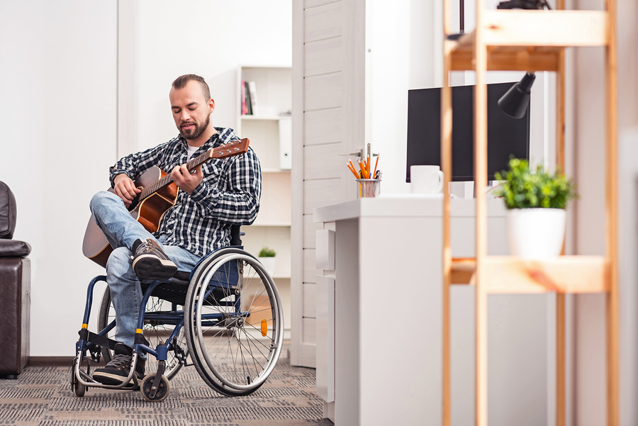 Man in a wheelchair playing guitar in a small apartment