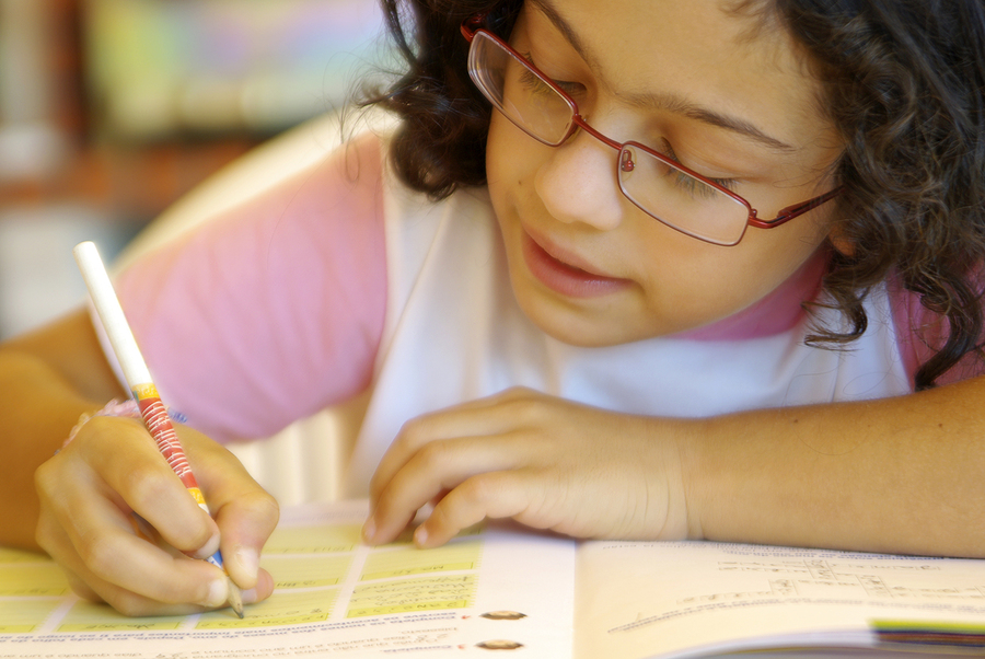 close up of a girl filling out a workbook