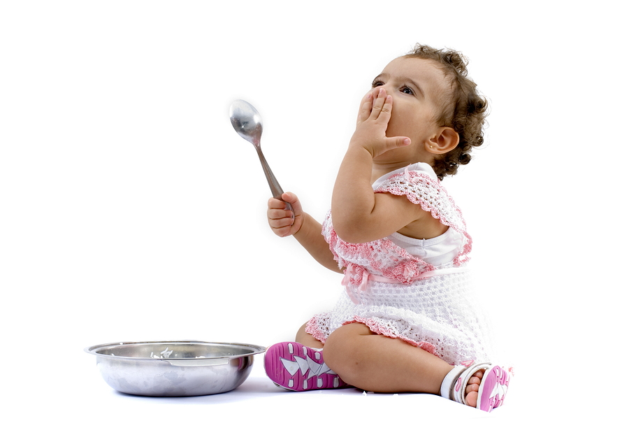 Toddler girl sitting on the floor eating from a bowl