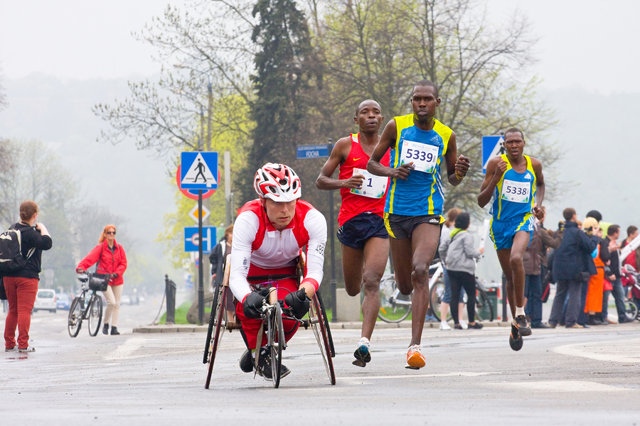 Wheelchair racer passing elite runners in marathone