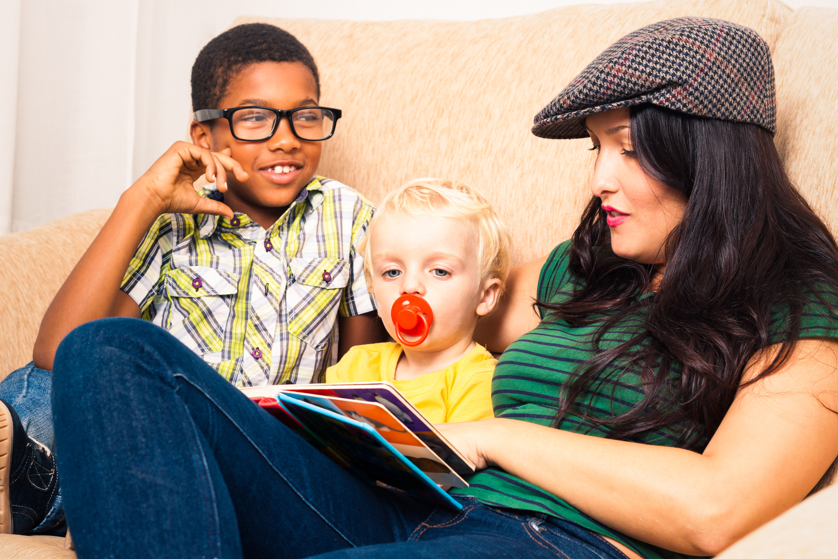 Childcare worker reading to children on the couch
