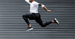 athletic person jumping in front of corrugated metal