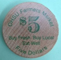 $5 wooden token with green writing