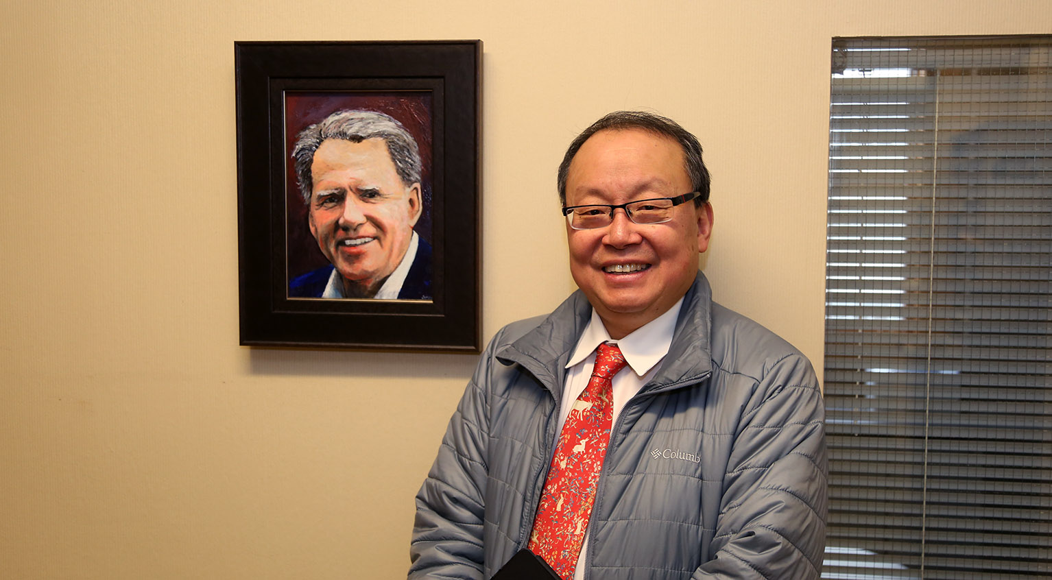 Jung Yoo, M.D., with portrait of Mark Richardson