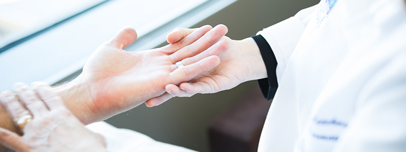 A dermatologist examining a patients hands