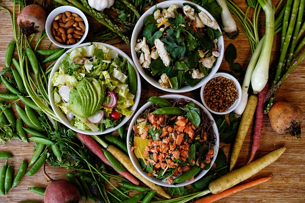 Fresh Salads with nuts and seeds in bowls surrounded by veggies laying on a table