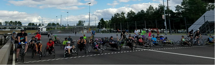Fifty handcyclist lining up at the Portland International Raceway startline at the beginning of a PDX Summer Handcycling Program