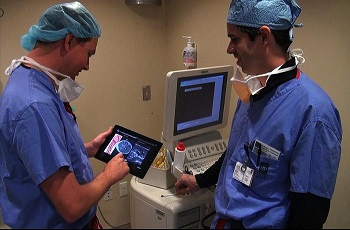 Two men in scrubs viewing an ultrasound image on a tablet
