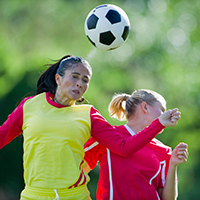 women soccer player heading the ball