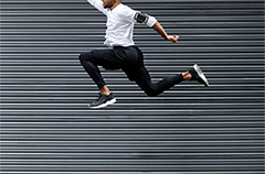 Person jumping in front of corrugated metal wall
