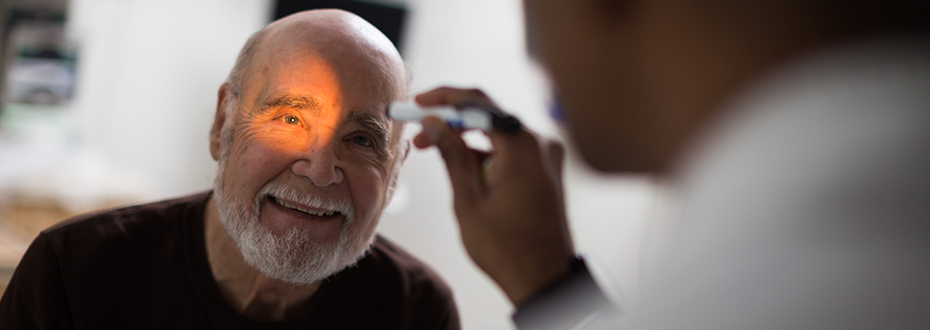 A doctor shinging a light into a patient's eye at the OHSU Knight Cancer Institute.
