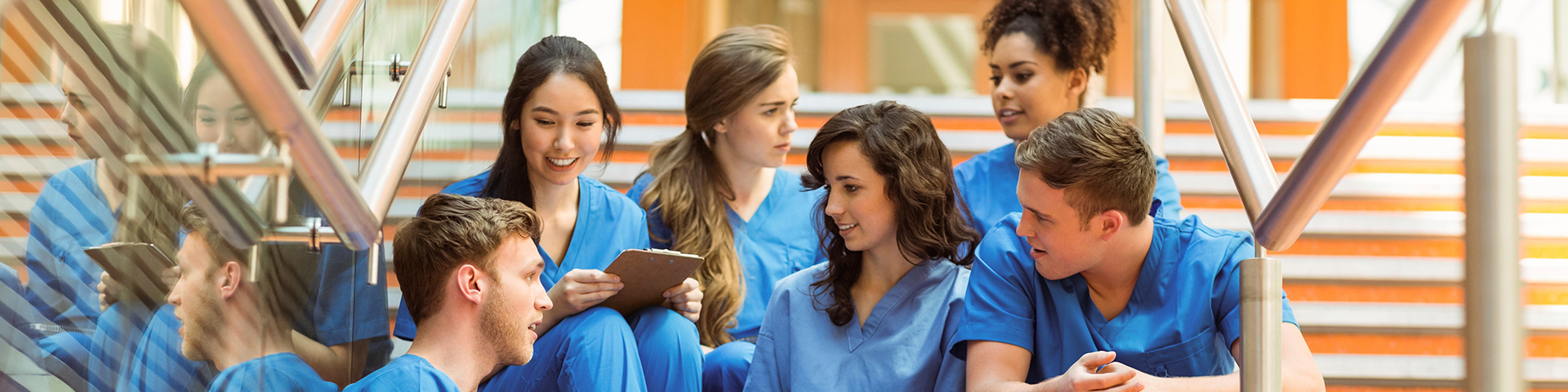 group of students in scrubs sitting on stairs
