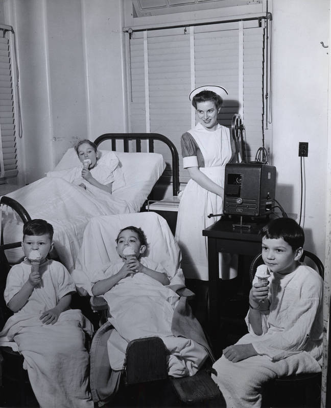 Doernbecher patients eating ice cream, nurse with film projector, circa 1940