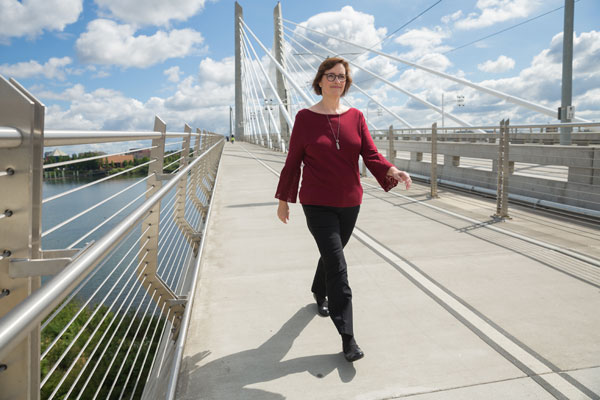 Alisa Brewster walking across the Tilikum Crossing Bridge