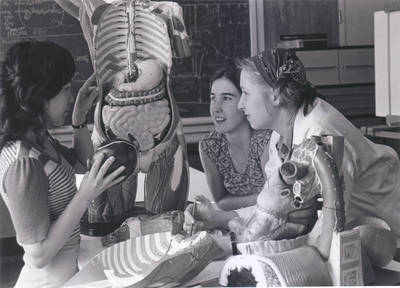 OHSU School of Nursing students studying an anatomical model, circa 1980s