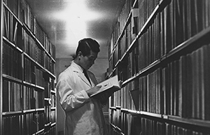 Student reading in library stacks, 1955