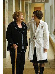 photo of clinician walking with patient in hospital hallway