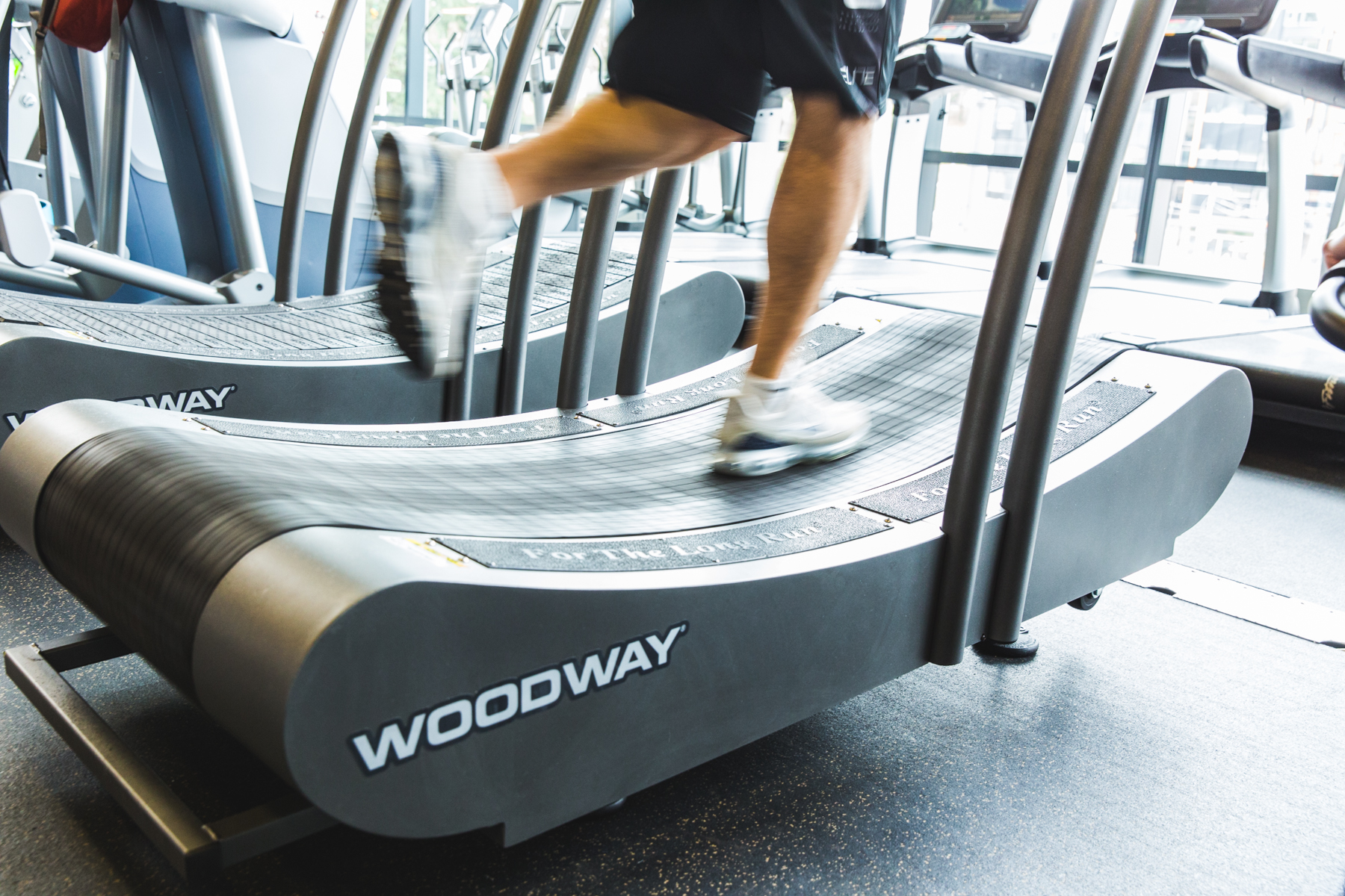 Runner in motion on march wellness & fitness center's Woodway curved treadmill.