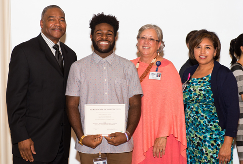 CURE-Equity Summer Internship Awards Ceremony: Intern displaying his award while posing with faculty.