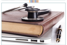 Book and stethoscope sitting on a laptop