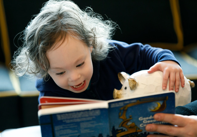 A child at play, looking at a book and holding a toy pig