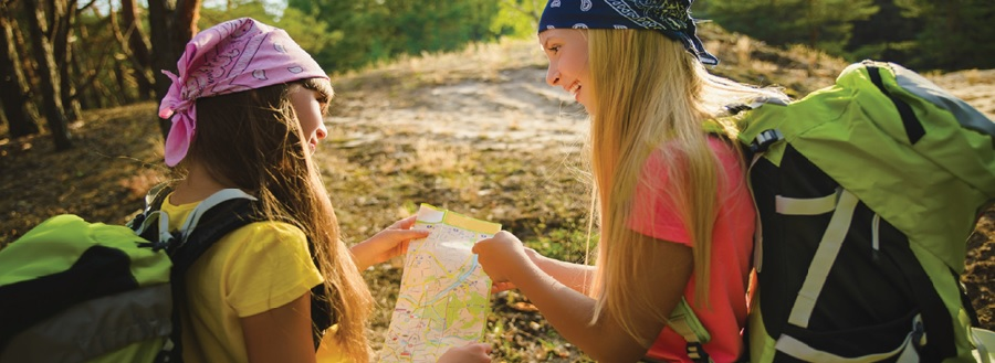 Two girls hiking on a trail stop to look at a map