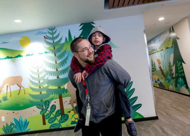 Jason Moreland giving son Noah a piggyback ride, colorful nature-themed mural in the background, lining the hallways