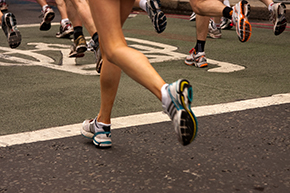 Photo of runners on pavement from the knee down.
