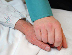 Elderly patient holding hands with caregiver