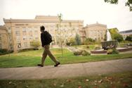 man walking in front of Mac Hall