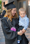 Graduate in gown and hat with a child