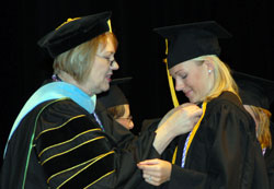 Female graduate getting a pin on her gown