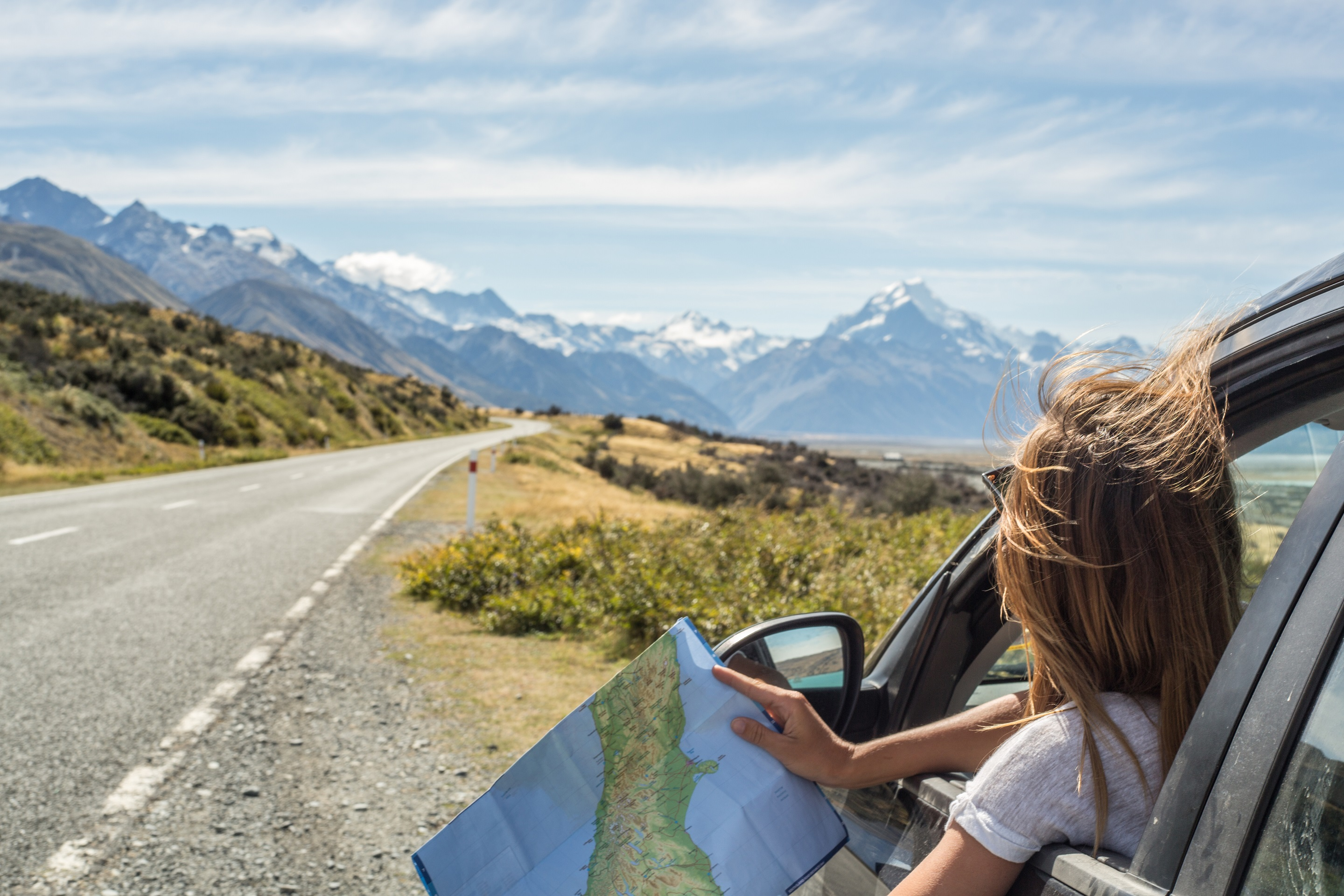 Woman in car looking at a map with mountains in the distance.
