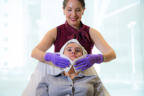 Aesthetician with a client doing a facial.