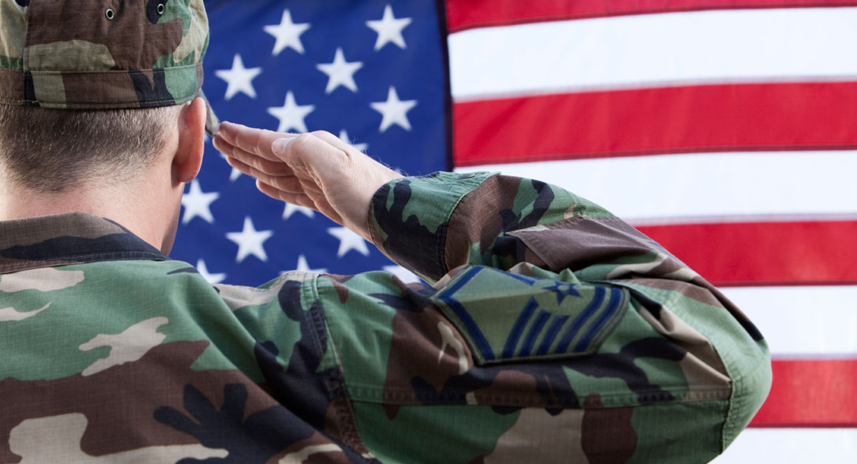 Soldier in camouflage saluting the US flag