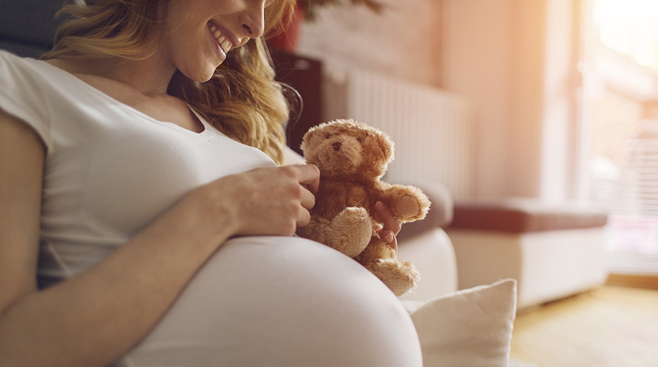 An expectant mother sits in a room, smiling at a teddy bear on her stomach.