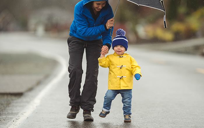A happy parent holds an umbrella for their smiling child while walking in the rain