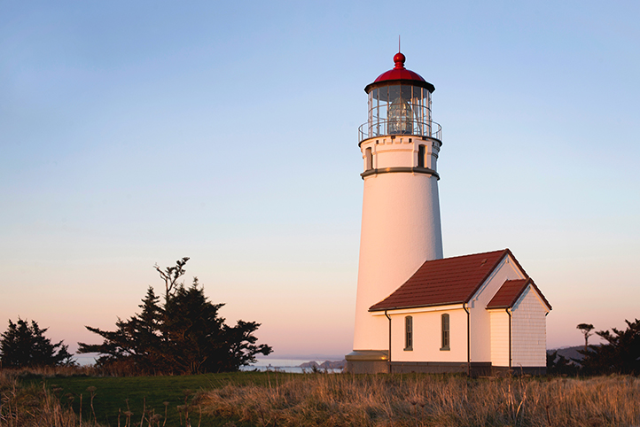 White lighthouse with red roof near the South Coast of Oregon at sunrise
