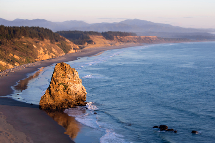 Overview of a beach with a haystack rock off of the South Coast of Oregon at sunrise