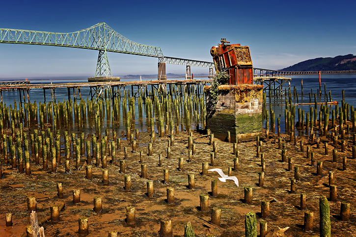 Large bridge and old pylons near the North Coast of Oregon in the midday sun