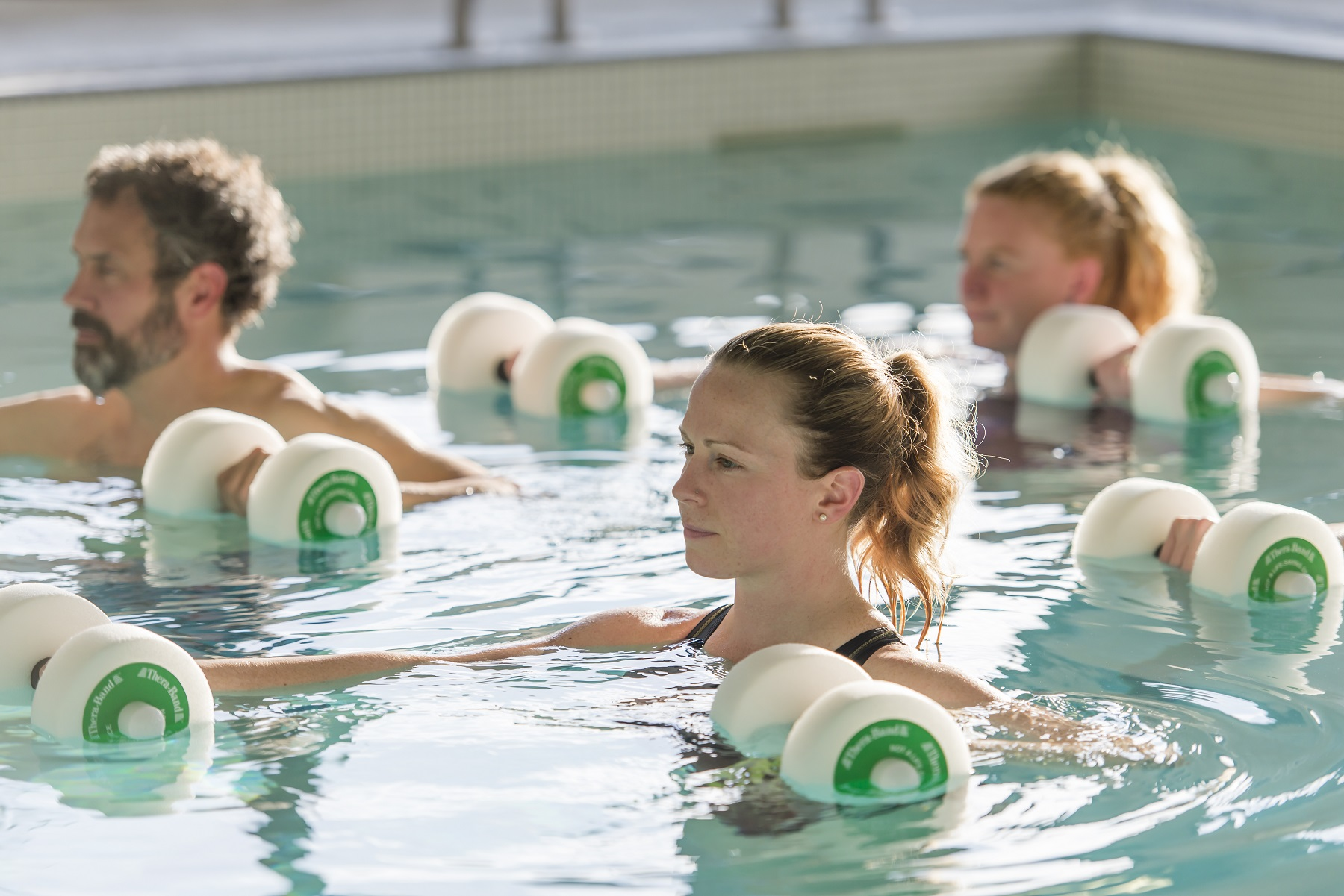 Three swimmers with water dumbbells enjoying march wellness & fitness center's therapy pool.